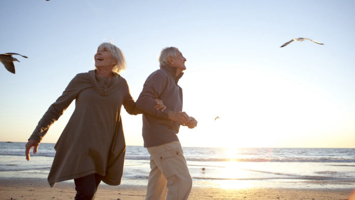 Old couple walking on the beach