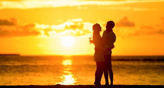 Couple kissing on the sand at sunset